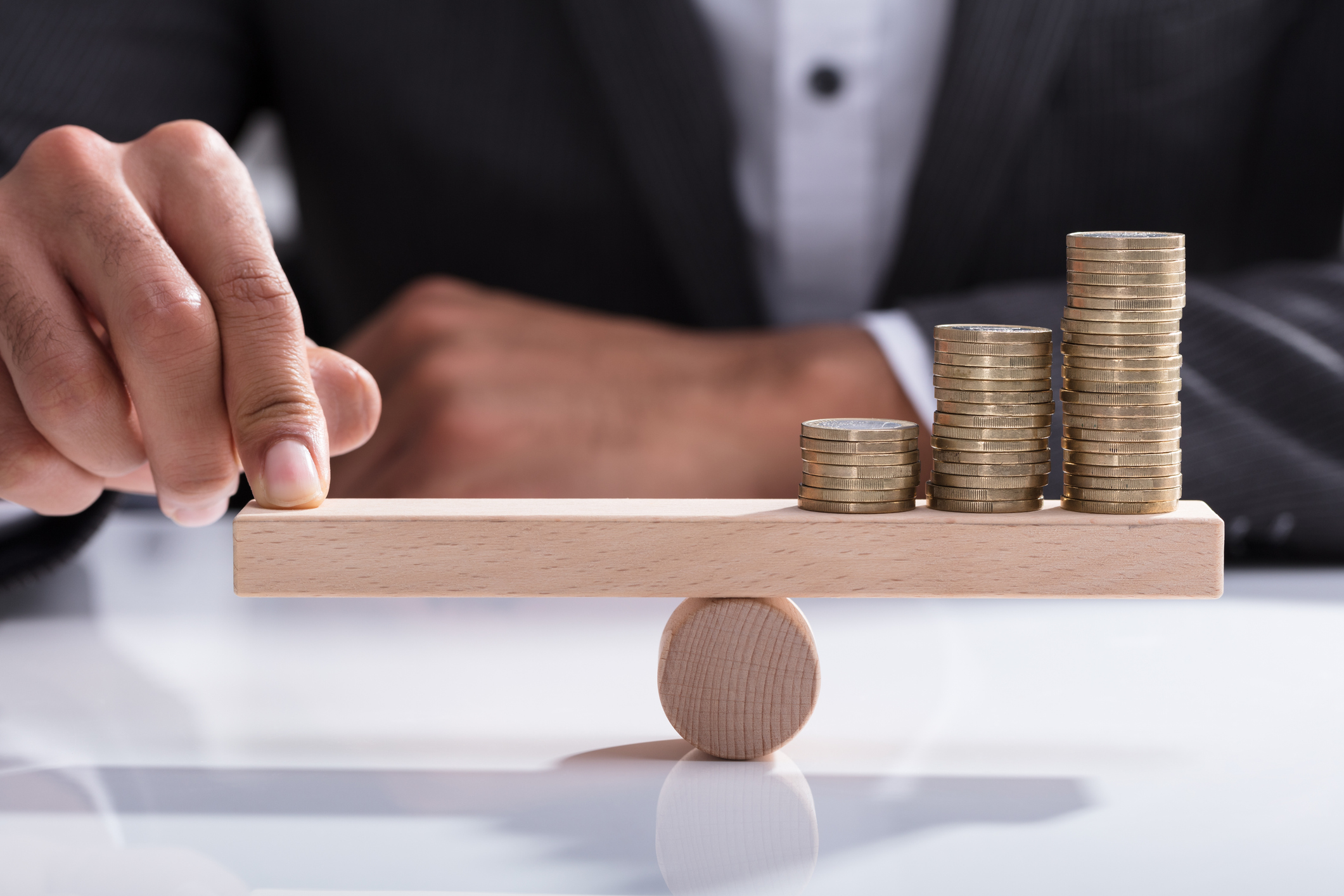 Businessperson Balancing Stacked Coins On Wooden Seesaw